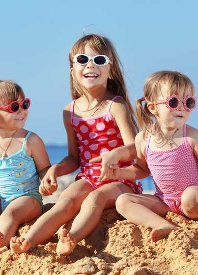 Three children smiling on the beach sand